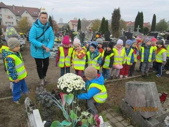 Przedszkolaki zapalają znicze i składają kwiaty